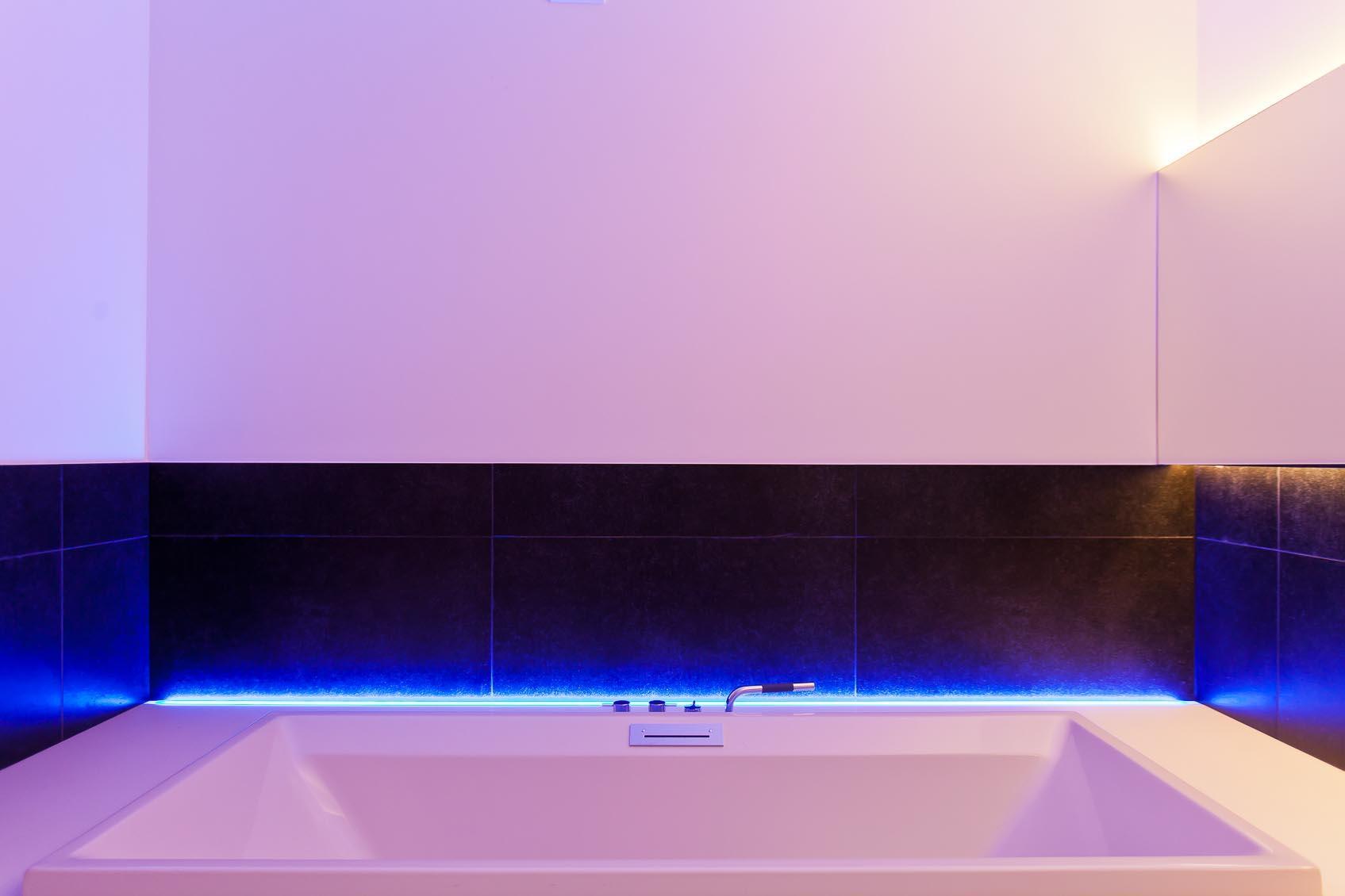 in deze design witte badkamer werd door maatwerk rgb ledstrip een speels kleur contrast toegevoegd