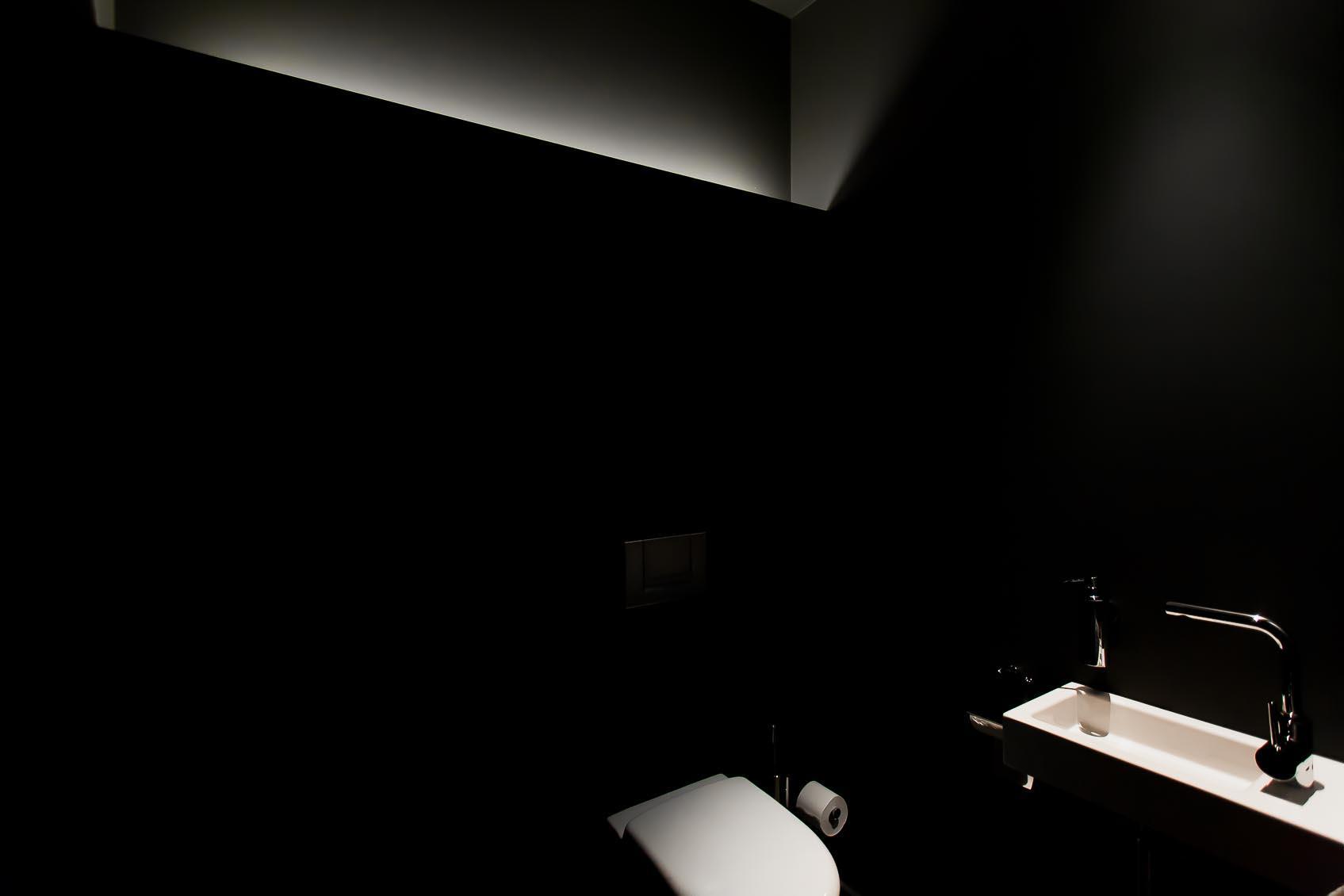 Maatwerk indirecte led verlichting in zwarte ruimte en accenten op witte wc en lavabo