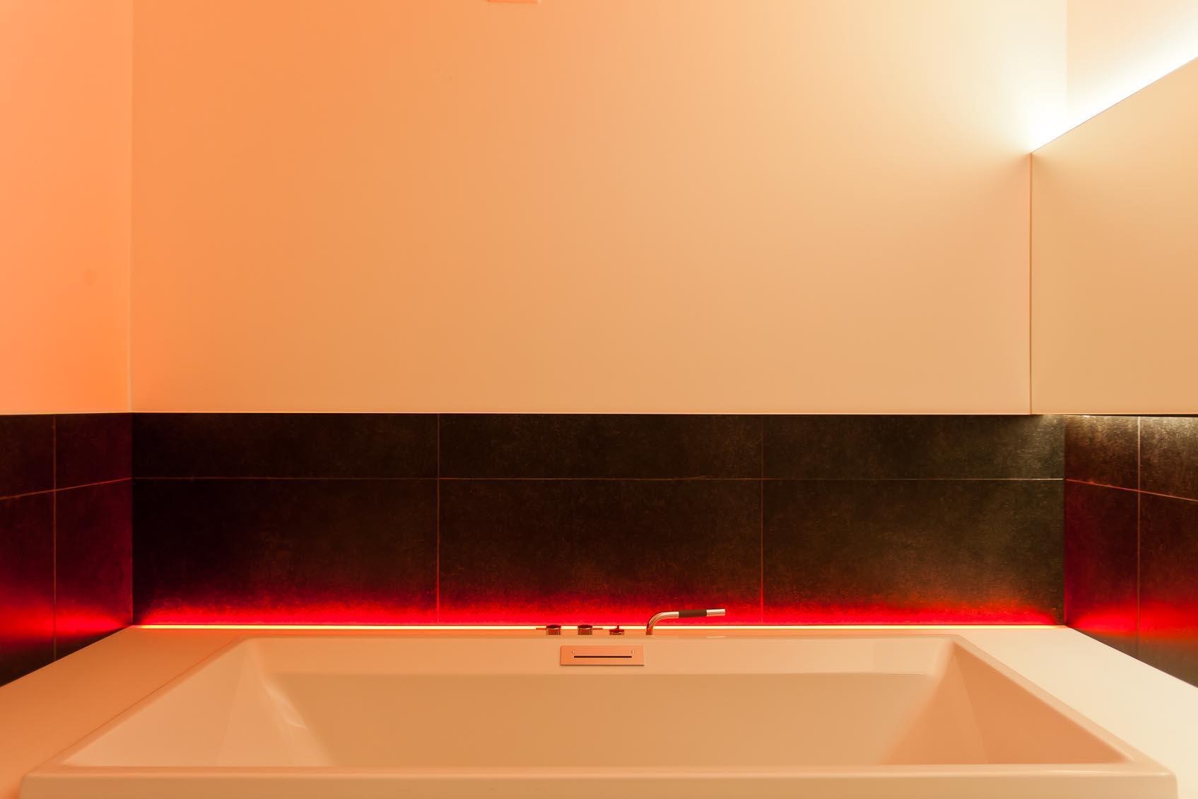 een speels kleur accent in strakke badkamer zorgt voor de juiste relaxerende sfeer